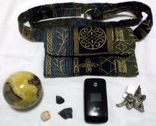 Clockwise - A fanny pack with multiple pockets (two zippered), a pewter fairy with crystals, a leopardite crystal, a dumoriterite crystal above, and to the left a sunstone crystal, and a septarian sphere.